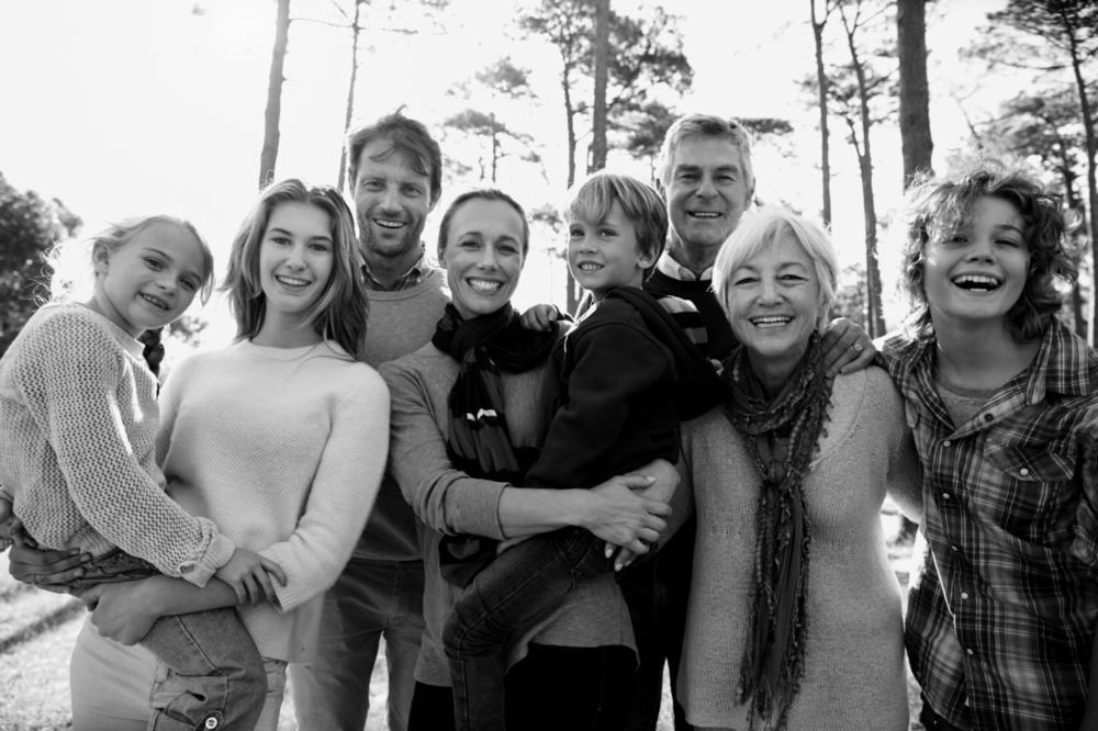 A family stands in the woods, smiling | family dentistry arlington tx