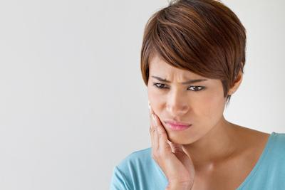 A woman holds her jaw | botox treatment arlington tx