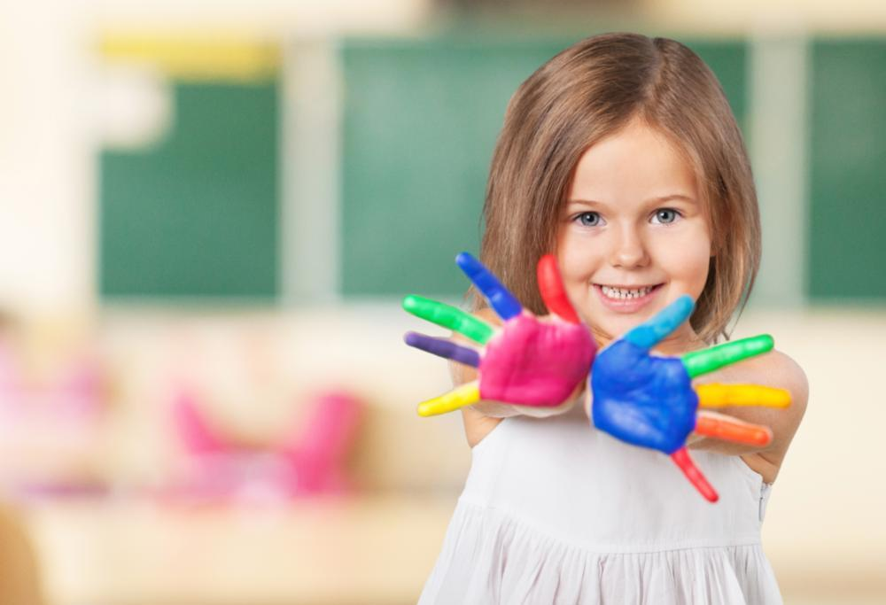 a girl holds up her painted hands | pediatric dentistry arlington tx