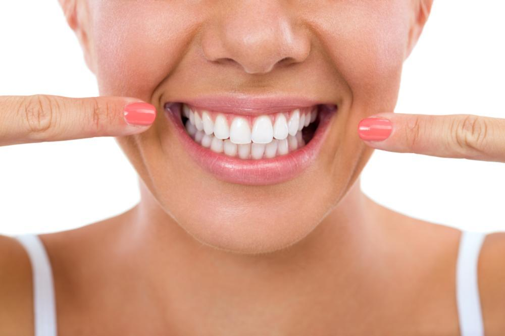 A woman points to her smile | Teeth Whitening Arlington TX