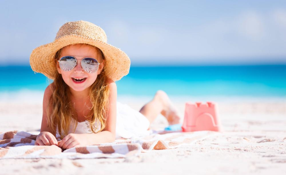 A girl lays on the beach | pediatric dentist arlington tx