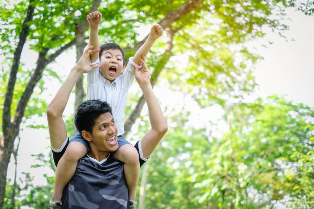 a boy sits on his father's shoulders | pediatric dentist arlington