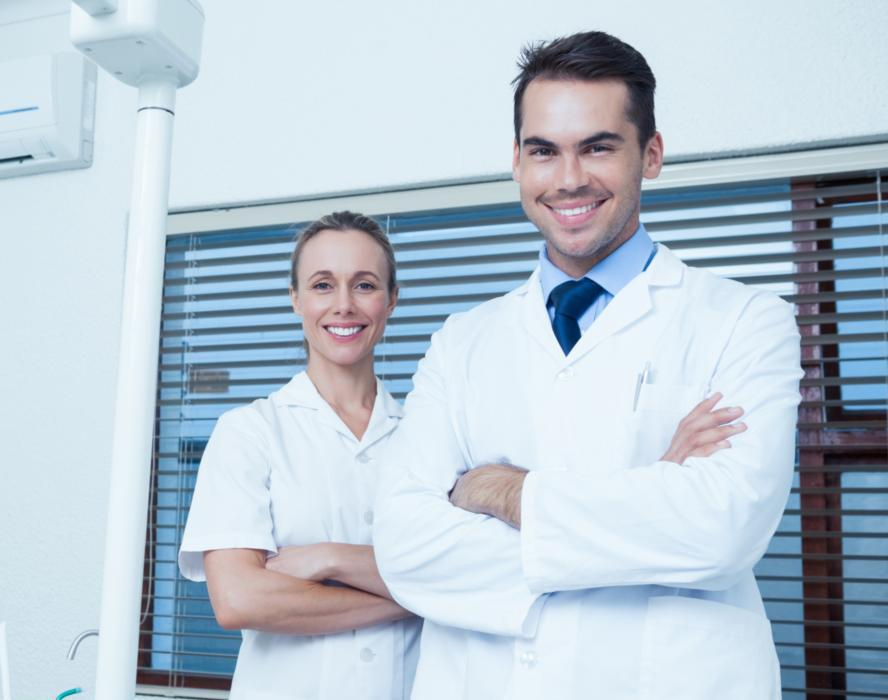 two medical professionals stand and smile | dentist arlington