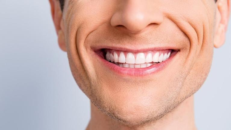 Toothy man flashes his wide smile showcasing his healthy, white teeth.