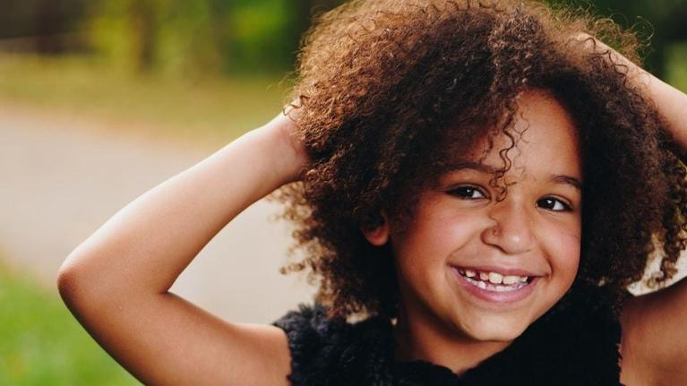 A child smiles in a park | Children's Dentistry Arlington
