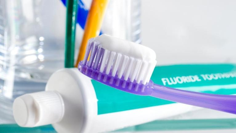 Close-up of teeth-brushing items in a bathroom including fluoride toothpaste