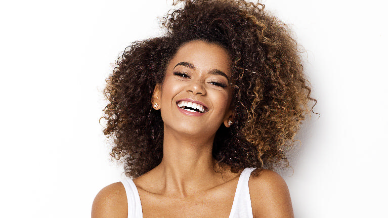 a woman smiles in front of a white backdrop | dental implants arlington tx