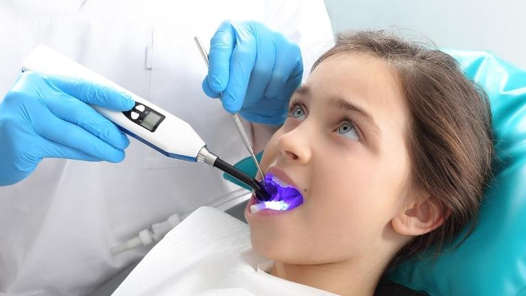 child in the dental office receiving laser dentistry