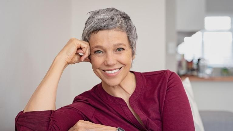 woman with good oral health and heart health smiling at the camera