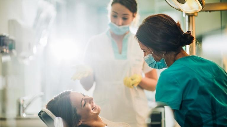 Young happy woman talking to a dentist before dental procedure to clean gum disease.
